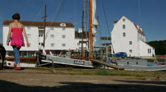 Traditional boats moored alongside the Woodbridge Tide Mill quayside - stock footage