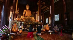 Couple praying to Buddha in Phan Tao Temple in Chiang Mai, Thailand. Zoom in. - stock footage