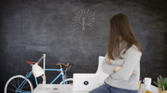 4K Woman sitting on desk with light bulb drawn on blackboard behind her Stock Footage