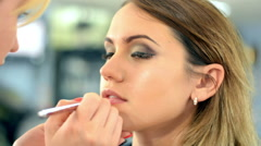 Makeup artist apply makeup to an attractive young woman Stock Footage