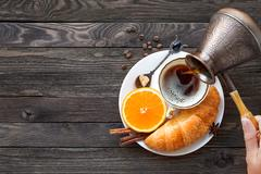 Continental breakfast - cezve and cup of hot coffee, croissant and orange. Ta Stock Photos