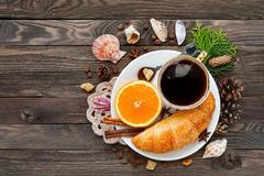 Continental breakfast - cup of hot coffee, croissant and orange. Tasty food o Stock Photos