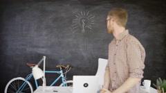 4K Man sitting on desk with light bulb drawn on blackboard behind him Stock Footage