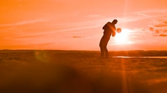 At sunset man tosses the ball up the slow motion video Stock Footage
