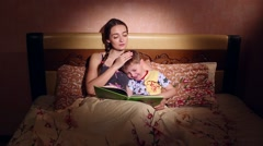 Mom Reads a Story to His Son Before Bedtime Stock Footage