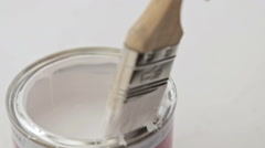 Paint brush dips into can of paint Stock Footage