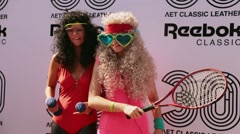 Two funny girls in wig gymnastic leotard posing for photo at summer festival Stock Footage