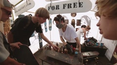 Skater give master skateboard for painting at summer festival. Griptape art Stock Footage