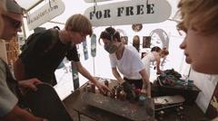 Skater give master skateboard for painting at summer festival. Griptape art - stock footage