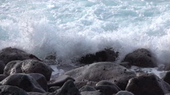 SLOW MOTION CLOSE UP: White ocean waves hitting and splashing on volcanic rocks Stock Footage