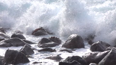 SLOW MOTION CLOSE UP: Ocean waves hitting and splashing on round volcanic rocks Stock Footage