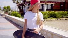 Tough young blond skateboarder walking on sidewalk - stock footage