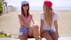 Gorgeous blond and brunette friends on stone wall Stock Footage