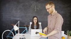 4K Man & woman in creative office with light bulb drawn on blackboard behind Stock Footage