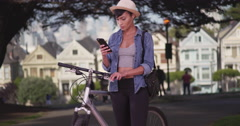 Pretty Hipster woman texting on cell phone in San Francisco Park on bike Stock Footage