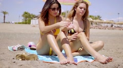 Young brunette sunbathing besides her friend Stock Footage