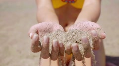 Young woman drizzling sea sand through her hands Stock Footage