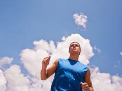 Young Man Doing Sports Runner Jogging Blue Sky - stock photo