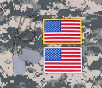 Small USA flag patches and ID tags on military battle dress uniform Stock Photos