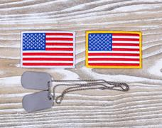 Small USA flag patches and military ID tags on rustic white wood - stock photo