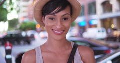 Happy smiling black woman holding hat on San Francisco city street - stock footage