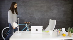 4K Businesswoman in creative office relaxing at desk with laptop & headphones Stock Footage