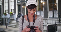 Woman with camera taking photo on Amsterdam city street Stock Footage