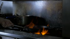 Slow motion frying pan with flames in commercial kitchen Stock Footage