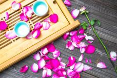 Petals of pink rose on old table Stock Photos