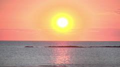 Large orange sun setting over water horizon Stock Footage