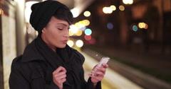 Woman on urban city subway metro platform at night texting on smartphone Stock Footage