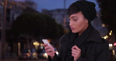 Woman in black overcoat on urban city street at night using texting app on cell Stock Footage