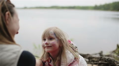 Little blonde girl with aqua makeup on her face depicts a cat for mom. Stock Footage