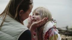 Mother looks at aqua make-up on the face of her little daughter. Stock Footage