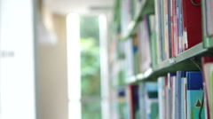 Asian girl looking for book, flip through and put back on library shelves Stock Footage