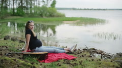 Expectant mother relaxing outdoors near the lake. Acoustic guitar is on a plaid. Stock Footage