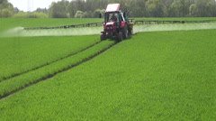 Tractor spraying fields with herbicides on spring evening Stock Footage