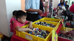 A kid going through a bucket of Legos at a Toy Fair & Exhibition in Kuala Lumpur Stock Footage