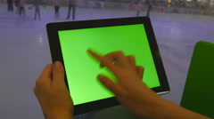 Hands using tablet pc with green screen. People skate on ice rink at background - stock footage