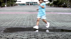 Young girl running through puddle after rain in park Stock Footage