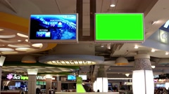 The weather network on tv and another with green screen inside food court at Stock Footage