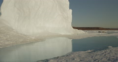Tilt up from reflection in melt water to glacier on sunny day Stock Footage