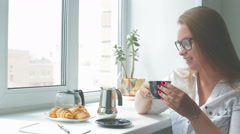 Young beautiful girl has breakfast on a sunny day Stock Footage