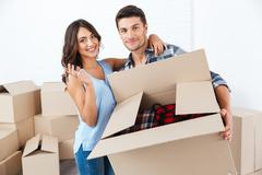 Couple showing keys to new home hugging looking at camera - stock photo