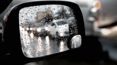 Rain drops on side mirror, Blurred of traffic in side mirror view on a rainy day Stock Footage