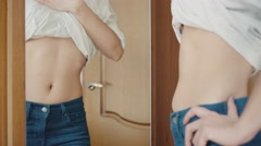 Girl flaunts her slim belly in front of the mirror at home Stock Footage