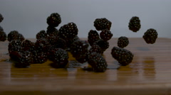 Blackberries falling and rolling onto a cutting board in slow motion - static Stock Footage