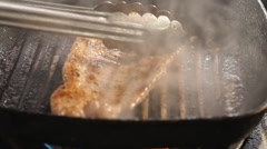 Chef turning thick juicy rib-eye steaks on hot grill Stock Footage
