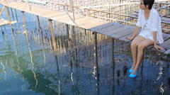 Asian woman sitting and look around fish farming Stock Footage