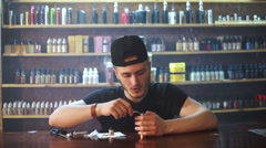 Young seller in vape shop is installing cotton in atomizer show window in Stock Footage